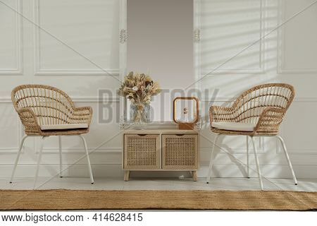 Living Room Interior With Wooden Commode, Mirror And Wicker Chairs