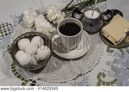 View From Above. There Are White Carnations On A White Tablecloth, A Cup Of Coffee On A White Saucer