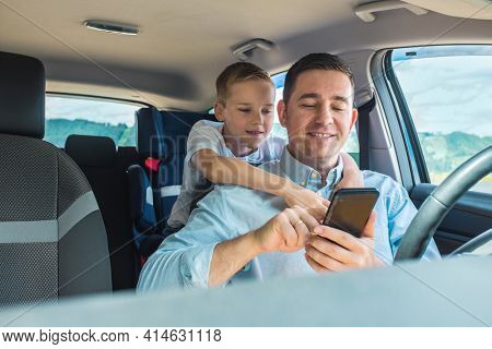 Happy father and son sitting in car and using smartphone in summer sunny day. Happy family travellers.