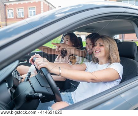 Three Friends Go On A Trip. Caucasian Women Drive In A Car And Point Fingers In Surprise.