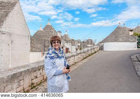 Happy Caucasian Woman Visiting Trulli Village In Alberobello, Italy.