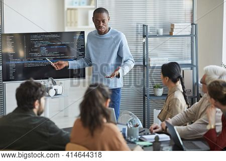 Portrait Of Emotional African-american Man Giving Presentation In Office To It Team And Pointing At