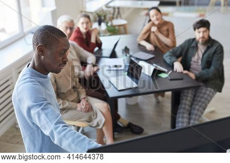 High Angle Portrait Of African-american Man Giving Presentation In Office To Diverse Business Team A
