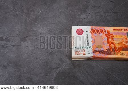 Russian Rubles A Large Bundle On A Gray Background. A Bundle Of Five-thousand-ruble Notes. Place For