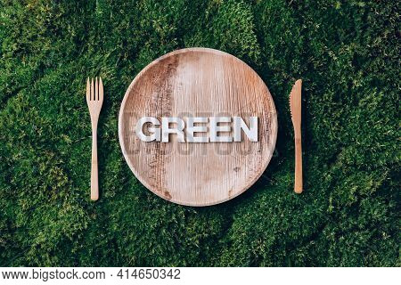 Wooden Disposable Tableware From Natural Materials With Word Green, Wooden Spoon, Fork On Green Moss