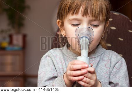 A Little Girl Close-up In A Mask Breathes A Medicinal Solution From A Nebulizer, Inhalation For Pneu