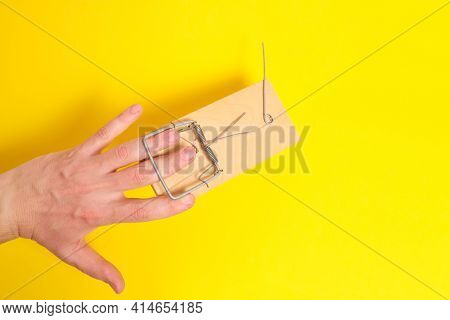 Man Hand Was Caught In A Mousetrap On A Yellow Background.concept, Risks, And Failures