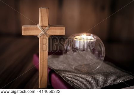The Cross And The Light Of The Candle Placed On The Scriptures. Christian Religious Concepts The Cru