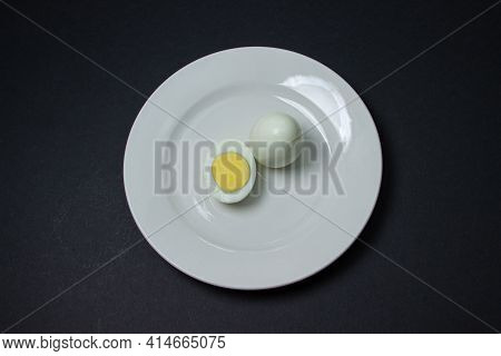 A Boiled Egg Cut In Half On A Plate. Healthy Breakfast. Boiled Egg On Black Background