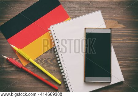German National Flag, Notebook, Phone, Two Simple Pencils On Brown Wooden Desk. Top View, Flat Lay.