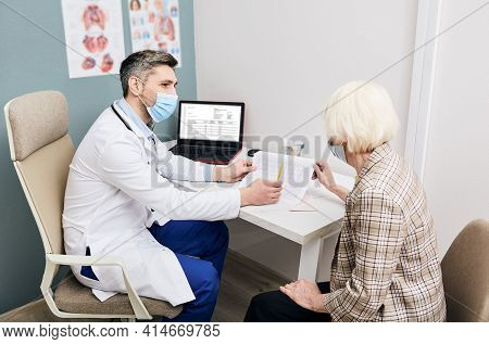 Doctor Wearing In Medical Mask Consults A Senior Woman On The Results Of A Cardiogram And Tests. Dia