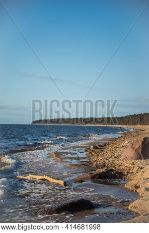 The Shore Of The Sea Beach Which Is Washed By The Waves Of Blue Sea Water Forming White Foam And Was