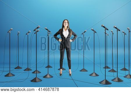 Business Conference Concept With Businesswoman Speaker Among Floor Stand Microphones On Blue Backgro