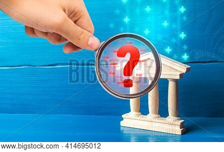 A Hand With A Magnifying Glass Inspects Bank And Finds Violations. Audit Of Commercial Banks. Stop M