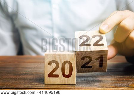 Hand Flips A Block Changing 2021 To 2022. New Year Beginning. Holidays And Christmas. Trends And Cha