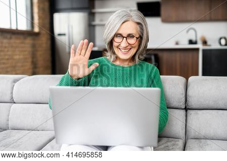 Modern Mature Woman In Touch With A Family, Friends Or Colleagues Via Video Connect. Senior Female U