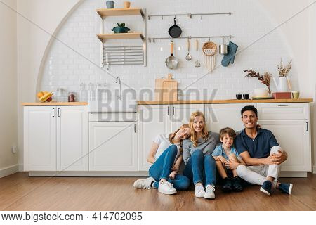 Happy Family Portrait Of Young Caucasian Couple Sitting On Wooden Floor In Modern Kitchen Leaning Ag