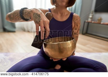 Girl Sitting In The Lotus Position And Playing The Sound Bowl Of Buddhism. Young Girl Sitting And Me