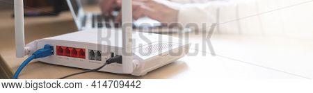ฺฺbanner Horizontal Shot Of Internet Router On Working Table With Blurred Man Connect The Cable At T