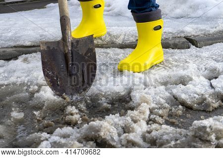 Man In Rubber Foam Boots Cleaning The Track From Old Snow. He Shovels Off Dirty Wet Snow With A Shov