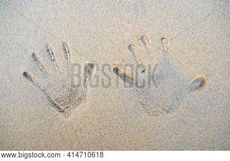 Hand's Prints On The Sand Of The Beach With Sea Wave. Top View. Two People's Hands Marks On The Sand