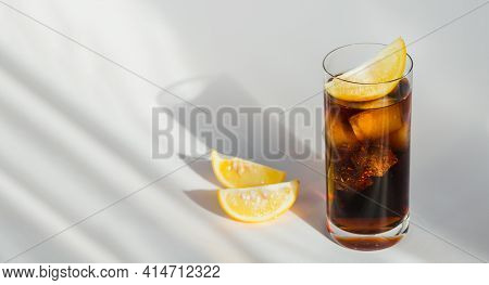 Glass Of Cola With Ice And Slices Of Lemon On White Background