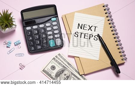 Next Steps Written On A Card Lying On The Table Next To A Notebook And A Pen