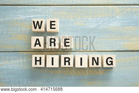 We Are Hiring Text On Wooden Blocks Against Blue Background. Concept Of Human Resources Recruitment,