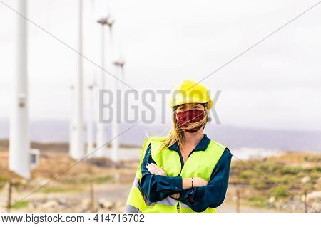 Front View Of Young Woman Engineer Working In Wind Turbine Farm. Clean Energy, Renewable Energy And