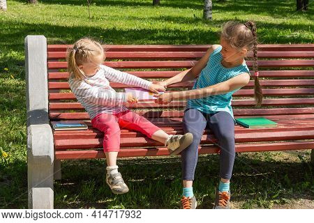 Two Kids Quarrel On A Bench In The Park. Two Little Girls Do Not Want To Share And Are Fighting Over