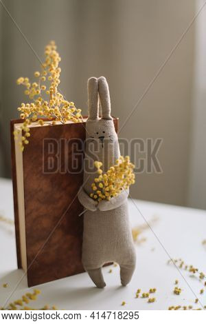 A Book And A Funny Handmade Bunny Rabbit Toy With Mimosa Flowers. Easter Gift Concept. House Decor,