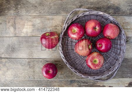Red Apples On The Tray And On The Table. Fruit On An Old Wooden Background. Wicker Dishes With Food