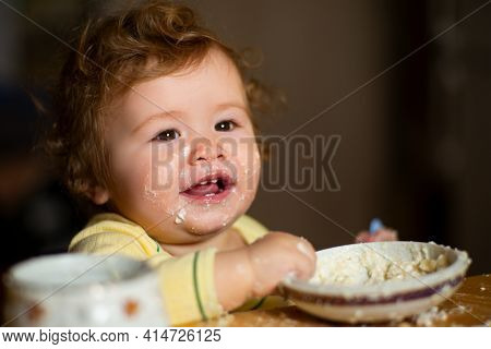 Cheerful Smiling Child Child Eats Itself With A Spoon Baby Eating With Dirty Face. Smiling Little Ch