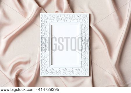 Chic Style Photo Frame With Empty Space For Text On Silk Fabric. Flat Lay, Top View, Copy Space.