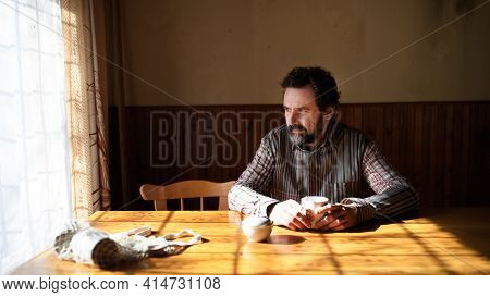 Portrait Of Unhappy Poor Mature Man Reading Newspapers Indoors At Home, Poverty Concept.