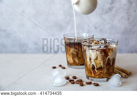 Two Glass Iced Coffee With Cream Pouring From The Top, Ice Cubes, Cocktail Straws And Coffee Beans O
