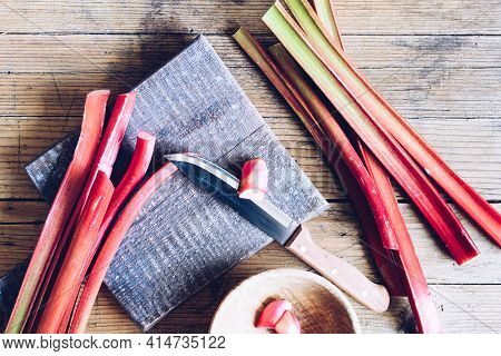 Bundle Of Fresh Picked Stalks Of Organic Rhubarb On Cutting Board With Knife On A Wooden Background.