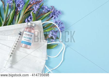 Vaccine, Syringe, Medical Face Masks And Snowdrop Flowers On Blue Pastel Background. Coronavirus, Co
