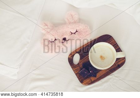 Cup Of Coffee With Chocolate And Cute Pink Sleep Mask On The Bed On Cozy Lazy Sunday. White Bedding