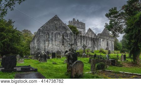 Graveyard And Tombs With Celtic Crosses In Front Of Old Ruins Of Muckross Abbey With Dramatic Storm