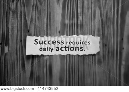 Success Requires Daily Actions. Inspirational Words On White Thorn Paper Note On Wooden Wall Backgro