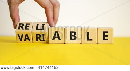 Variable Or Reliable Symbol. Businessman Turns Wooden Cubes And Changes The Word Variable To Reliabl