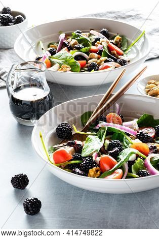 Close Up Of Blackberry Spinach Salads With Balsamic Vinaigrette, Against A Bright Sunny Window.