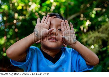 Asian Boy Plays  Hide And Seek Under The Tree, Close The Eyes With Hands