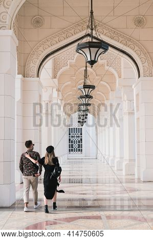 Abu Dhabi, Uae, March, 2021.young Couple,travelers-lovers Walk With Arms Linked Through Arched Entra