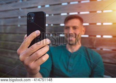 Young Happy Man With Smartphone Outdoors At Sunset. Man Using Modern Black Smartphone. Man Having A