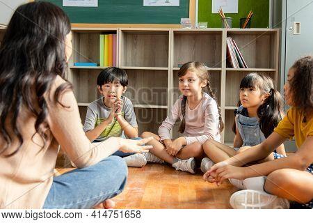 Diversity Elementary School Students Who Sit On The Classroom Floor Listen To Asian Female Teachers