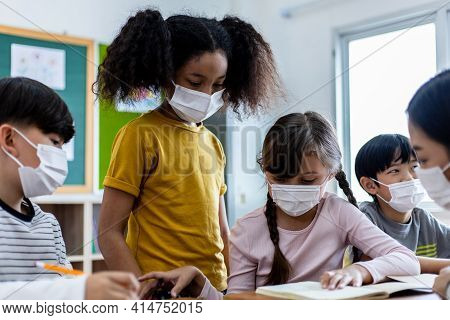 Diversity Of Children Students Wearing Medical Masks In The Classroom. An Asian Woman Teacher And St