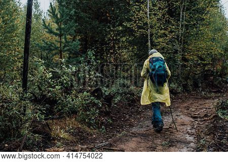 Rear View Of A Tourist In A Raincoat With A Backpack And A Stick Walking Along A Rocky Path In The A