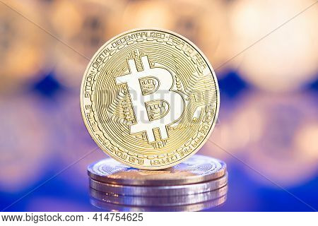 Gold Bitcoin Against Blue Background With Reflected Golden Coins. E-commerce Concept. Cryptocurrency